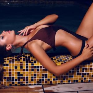 beautiful woman with dark hair in bikini posing in night swimmin